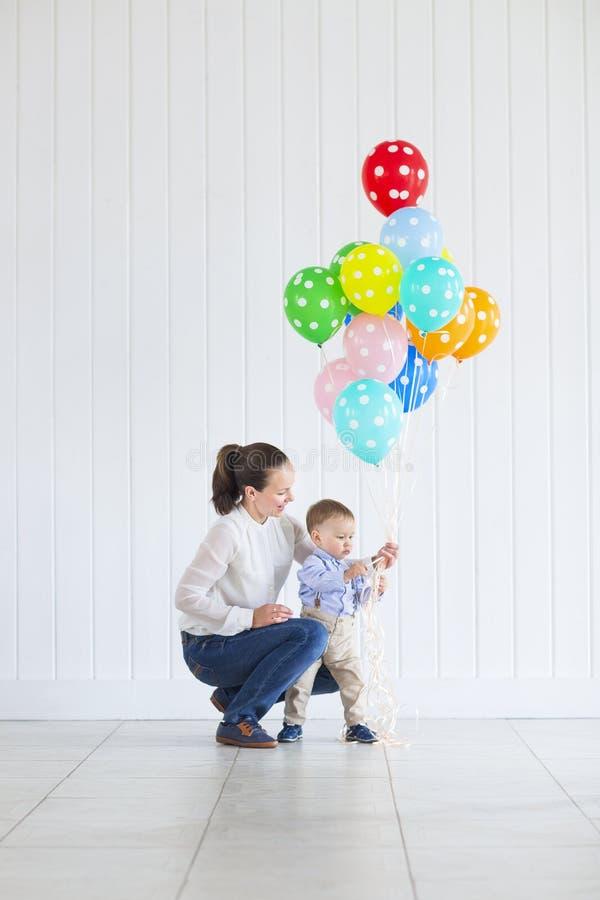 Pys med hans mamma som rymmer en grupp av kulöra ballonger royaltyfri bild