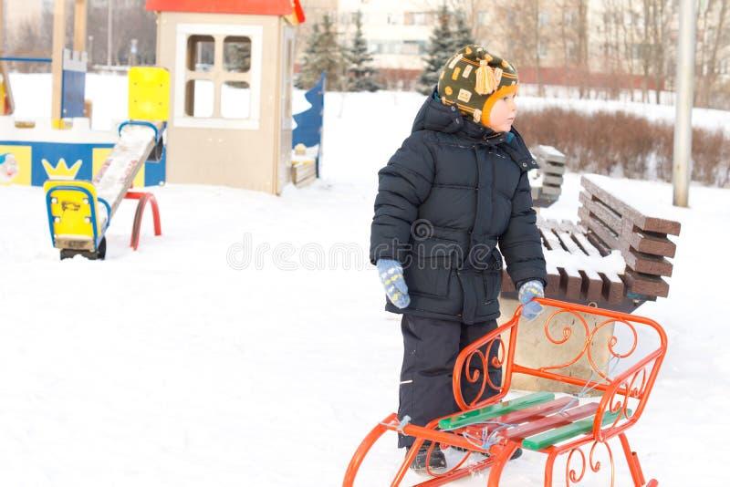 Pys med hans sled i vintersnow arkivfoton