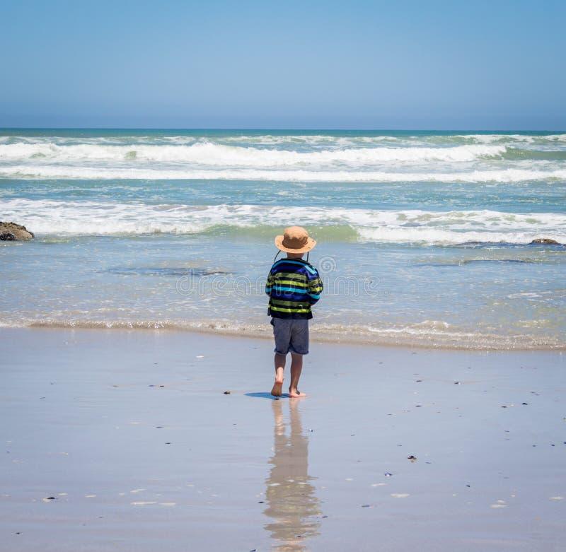 Pys med hatten som går in i havet på ljus solig dag fotografering för bildbyråer