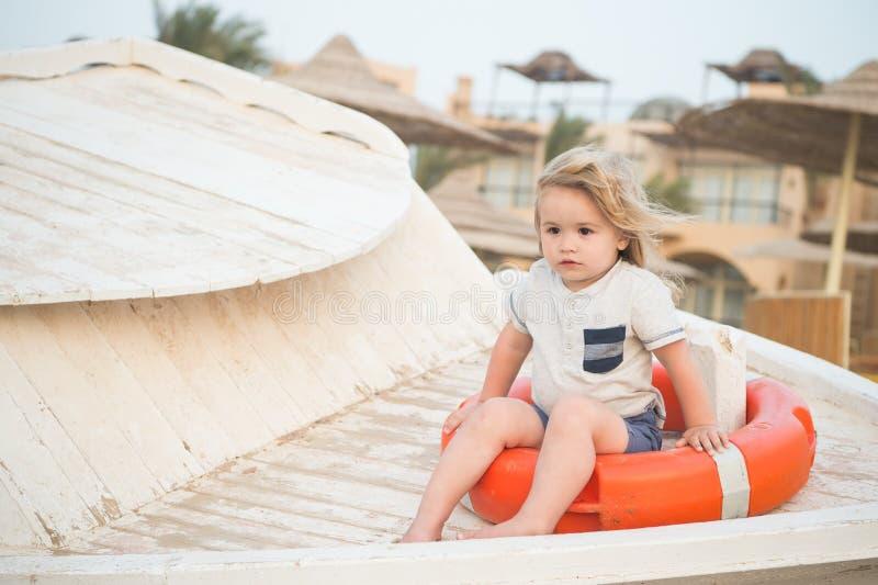 Pys med livboj på den tropiska stranden Barnet sitter i cirkelboj på solig dag Ungen med blont hår har utomhus- gyckel Sommarvaca royaltyfri foto