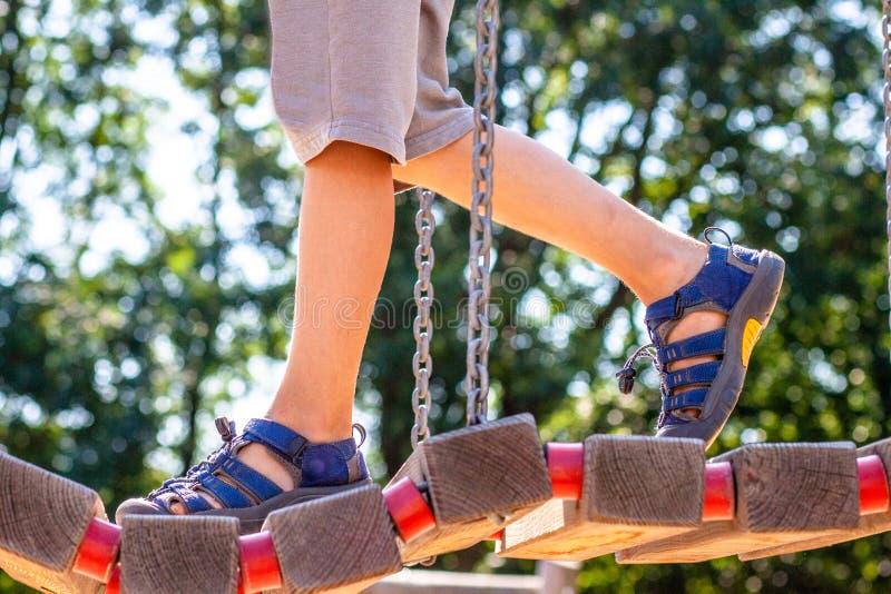 Pys med sandalen som går över bron royaltyfri bild