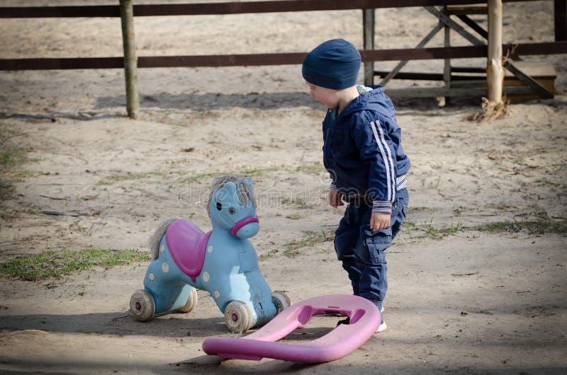 Pys och en leksakhäst på bakgrunden av en häck arkivbild