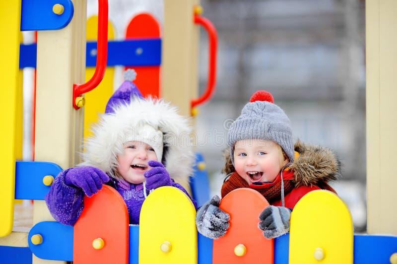 Pys och flicka i vinterkläder som har gyckel i det frialekplats arkivbild