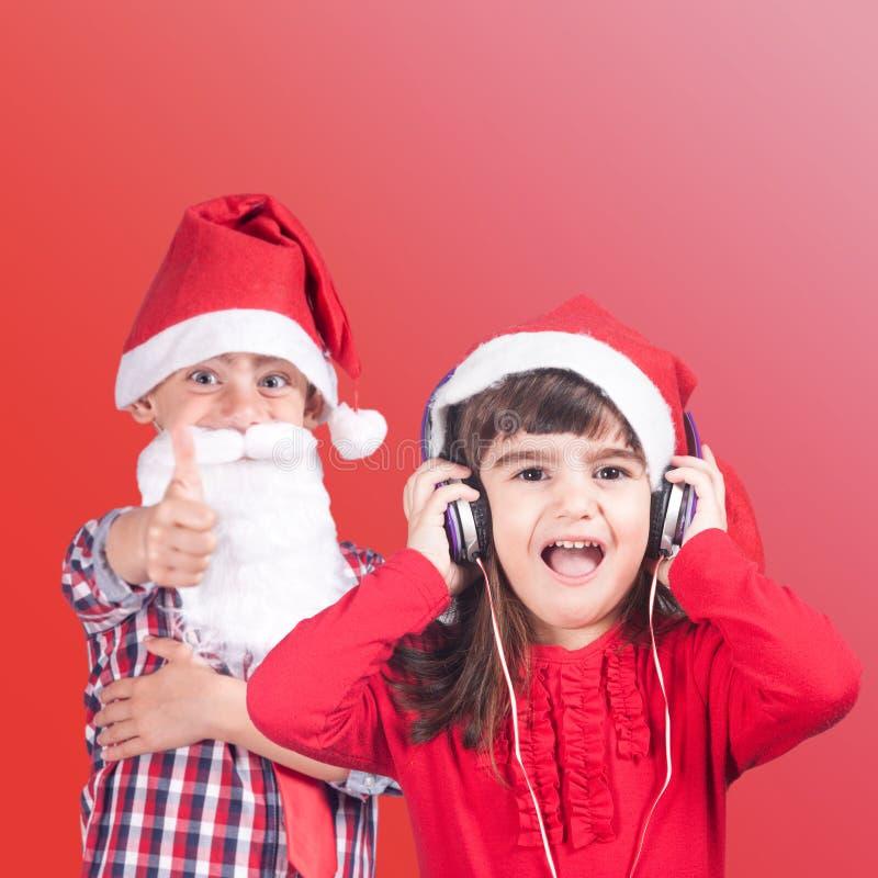 Pys och flicka som bär en jultomtenhatt royaltyfri foto