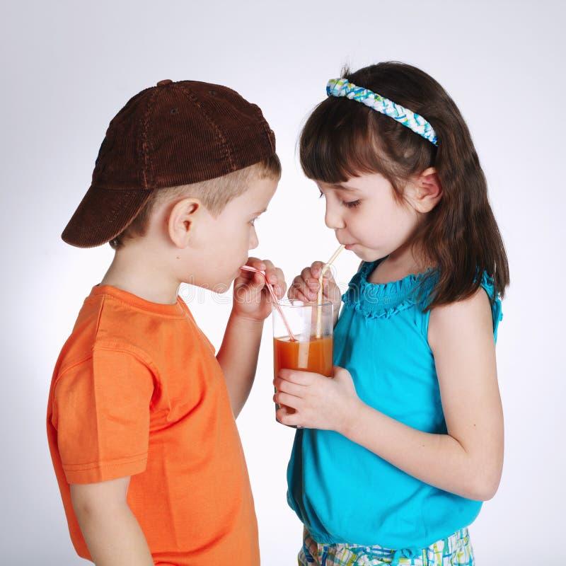 Pys och flicka som dricker fruktsaft royaltyfria bilder