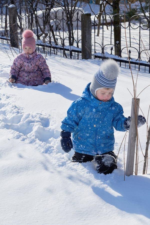 Pys och flicka som går i den djupa vita snön arkivbild
