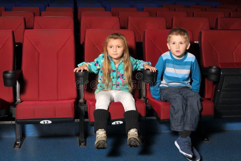 Pys och flicka som sitter och håller ögonen på en film royaltyfri foto
