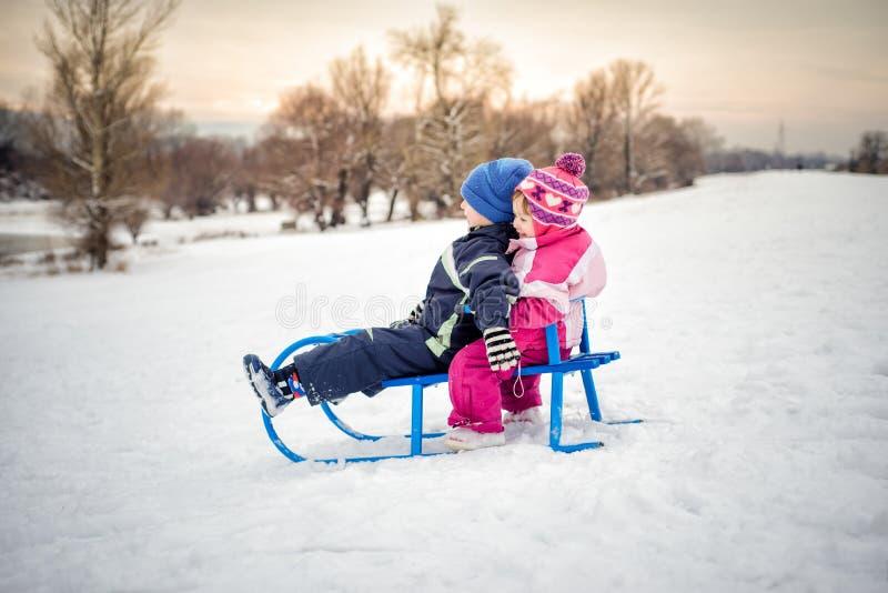 Pys och flicka som sledding i snöig fält royaltyfri bild