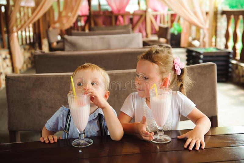 Pys och flicka som utomhus dricker milkshakar i ett kafé royaltyfria foton