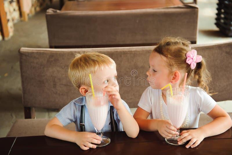 Pys och flicka som utomhus dricker milkshakar i ett kafé royaltyfri bild