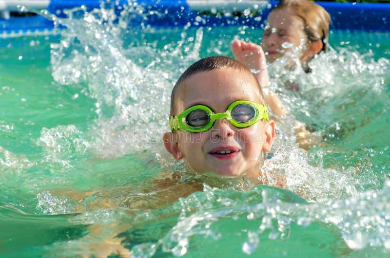 Pys- och flickasimning i simbassäng på solig sommardag arkivbilder