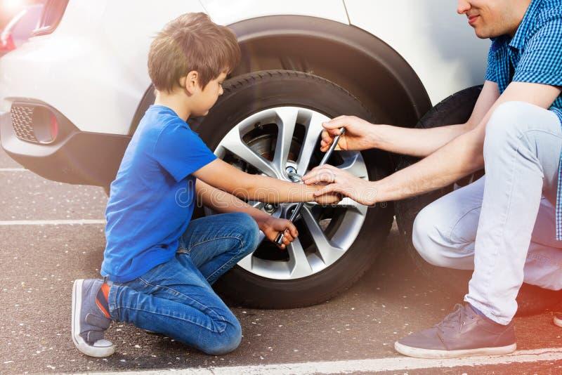 Pys och hans ändrande hjul för fader på en bil royaltyfria bilder