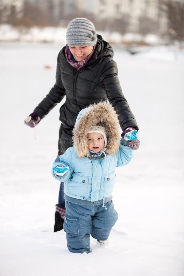 Pys och hans mom som har gyckel på en vinterdag royaltyfria foton
