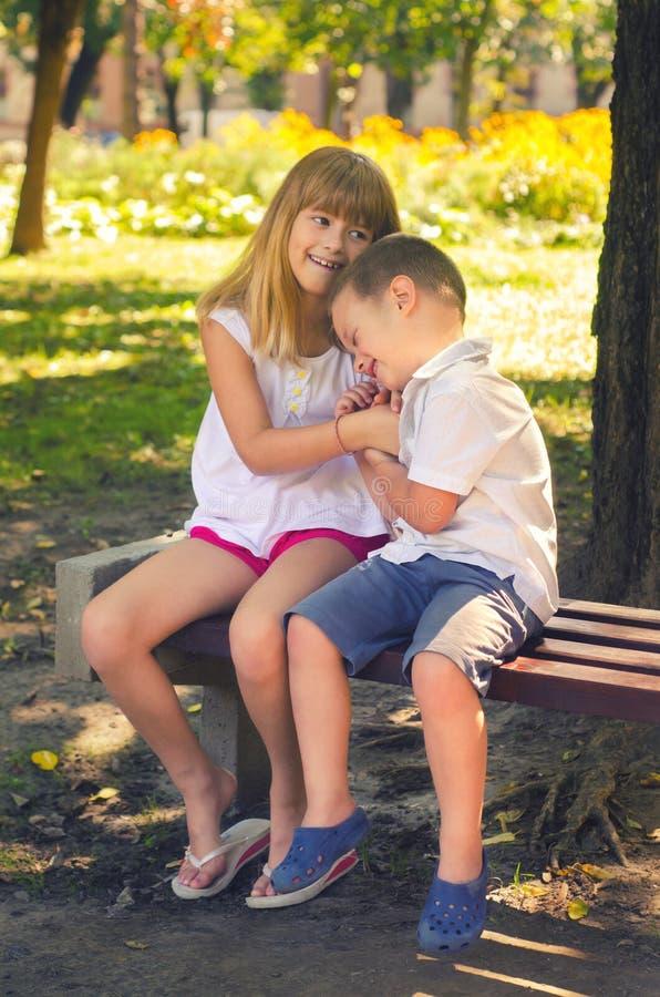 Pys och liten flicka som spelar i parkera på bänken på s arkivbild