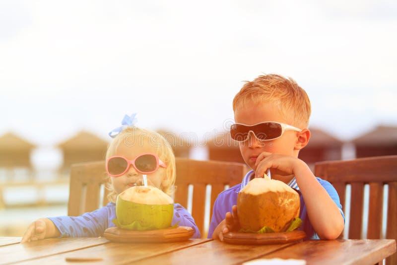 Pys- och litet barnflicka som dricker kokosnötcoctailen på stranden royaltyfri fotografi