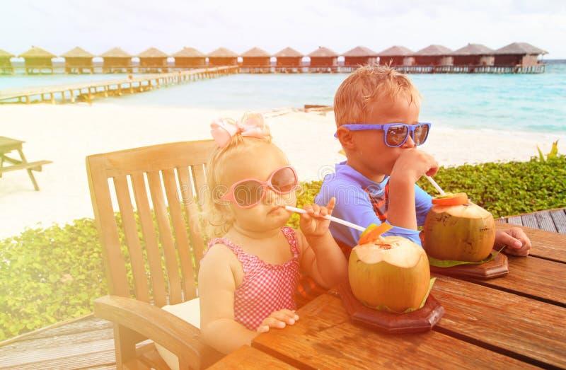 Pys- och litet barnflicka som dricker kokosnötcoctailen på stranden royaltyfri bild