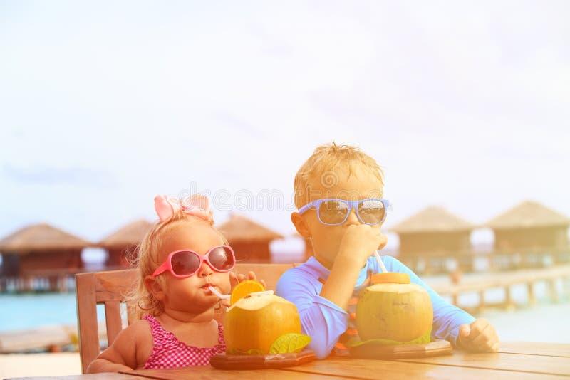 Pys- och litet barnflicka som dricker kokosnöten royaltyfria bilder