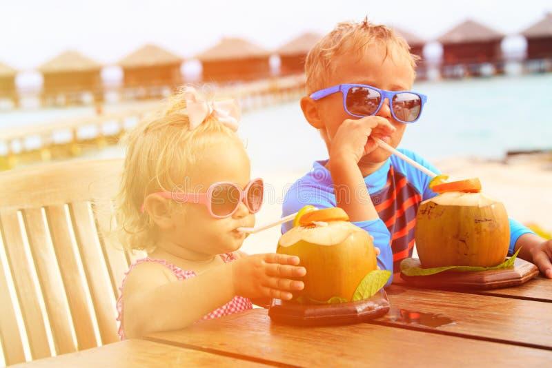 Pys- och litet barnflicka som dricker kokosnöten arkivfoto