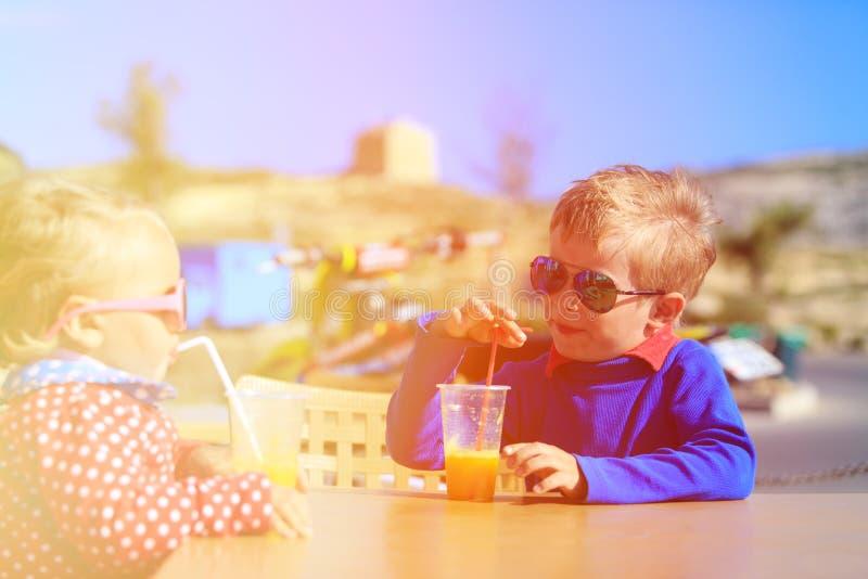 Pys- och litet barnflicka som dricker orange fruktsaft arkivfoton
