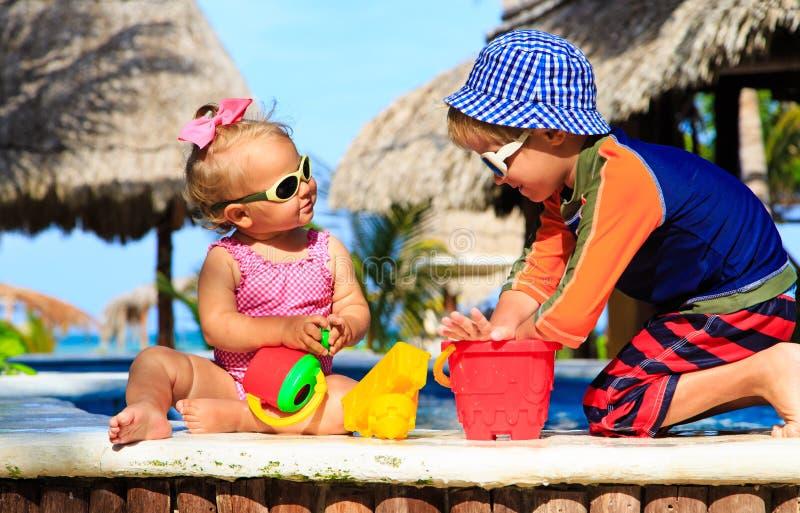 Pys- och litet barnflicka som spelar i simning arkivbild
