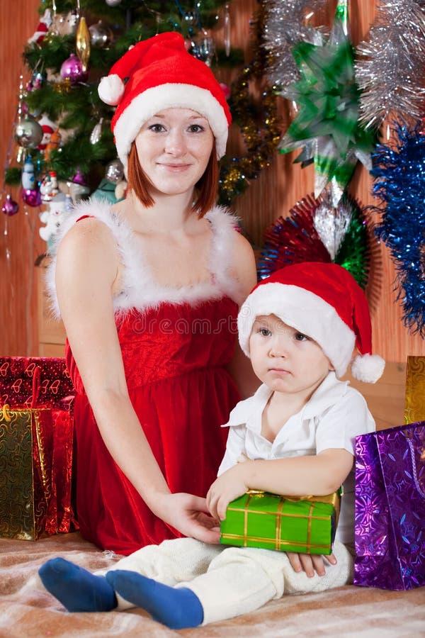 Pys och moder i den Santa hatten royaltyfria bilder