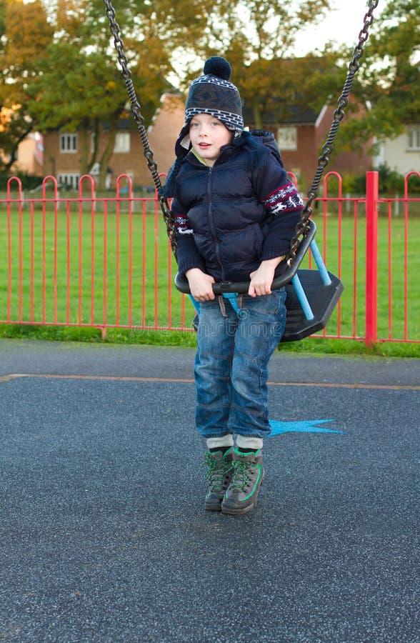 Pys på en swing på parken royaltyfri bild