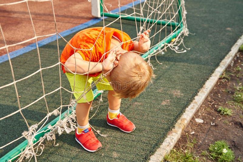 Pys på lekplats med ett raster av fotbollporten royaltyfri foto