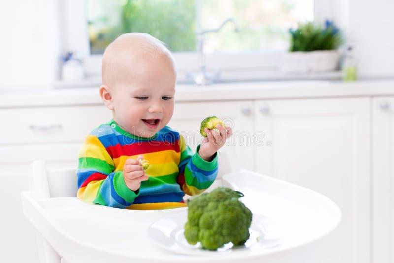 Pys som äter broccoli i vitt kök fotografering för bildbyråer