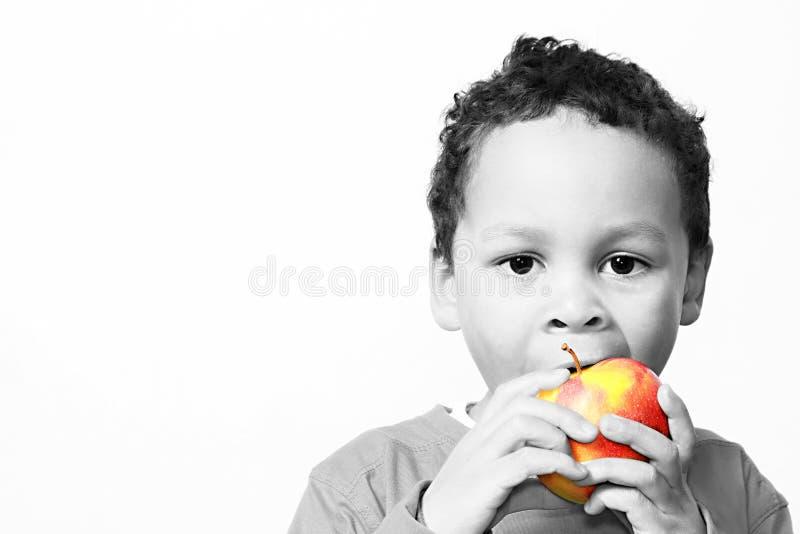 Pys som äter ett rött äpple som främjar sunt äta arkivfoton