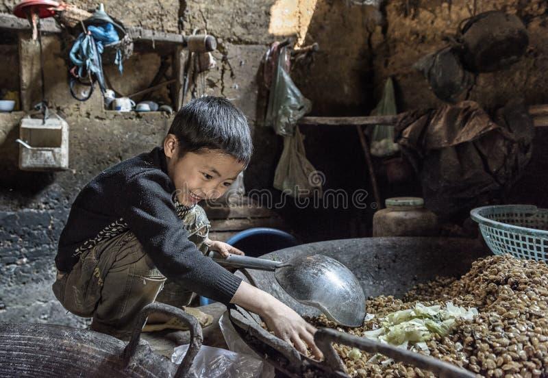 Pys som äter lagad mat mat inom hans traditionella hus i den Sapa byn, Vietnam arkivbilder