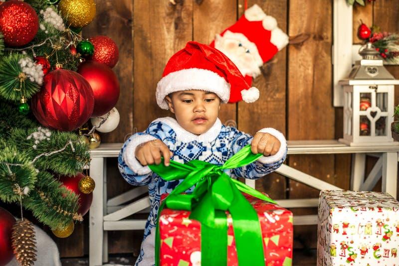 Pys som öppnar en julklapp arkivbilder