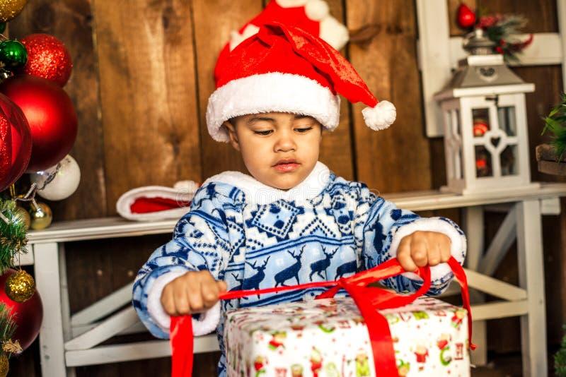 Pys som öppnar en julklapp fotografering för bildbyråer
