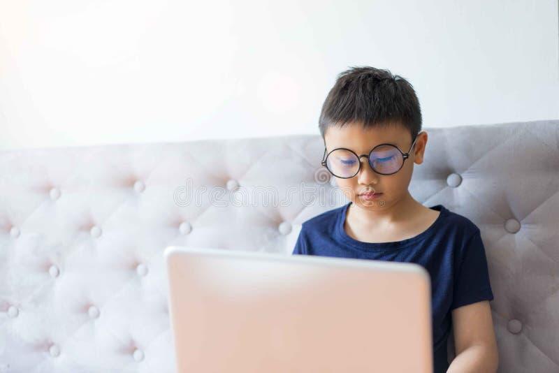 Pys som använder bärbara datorn som hemma lär om teknologi för utbildning arkivfoton