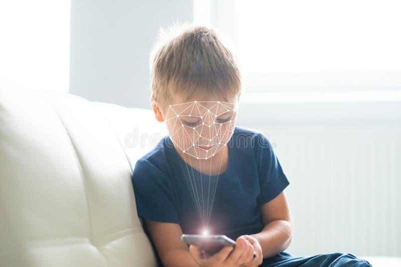 Pys som anv?nder framsidaID-legitimation Unge med en smartphone Digital inf?tt barnbegrepp royaltyfria bilder