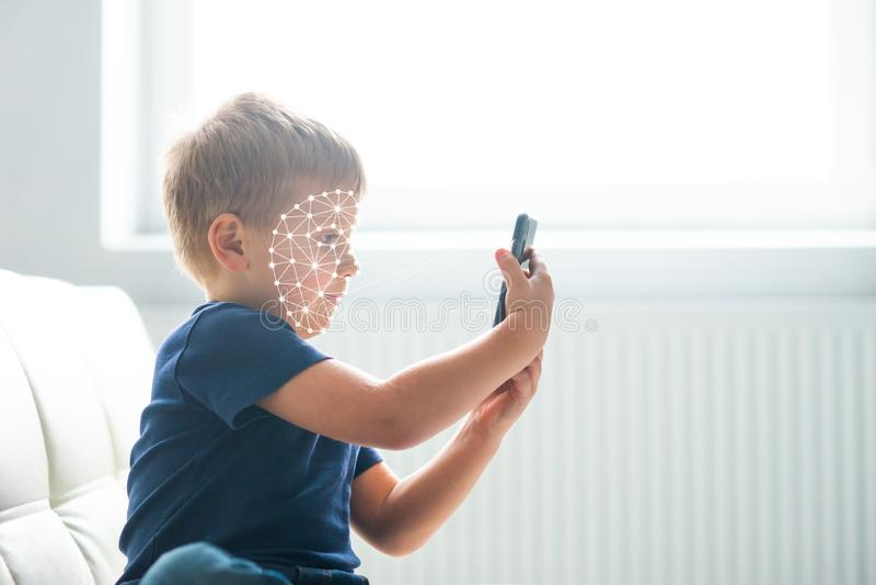Pys som anv?nder framsidaID-legitimation Unge med en smartphone Digital inf?tt barnbegrepp royaltyfri fotografi