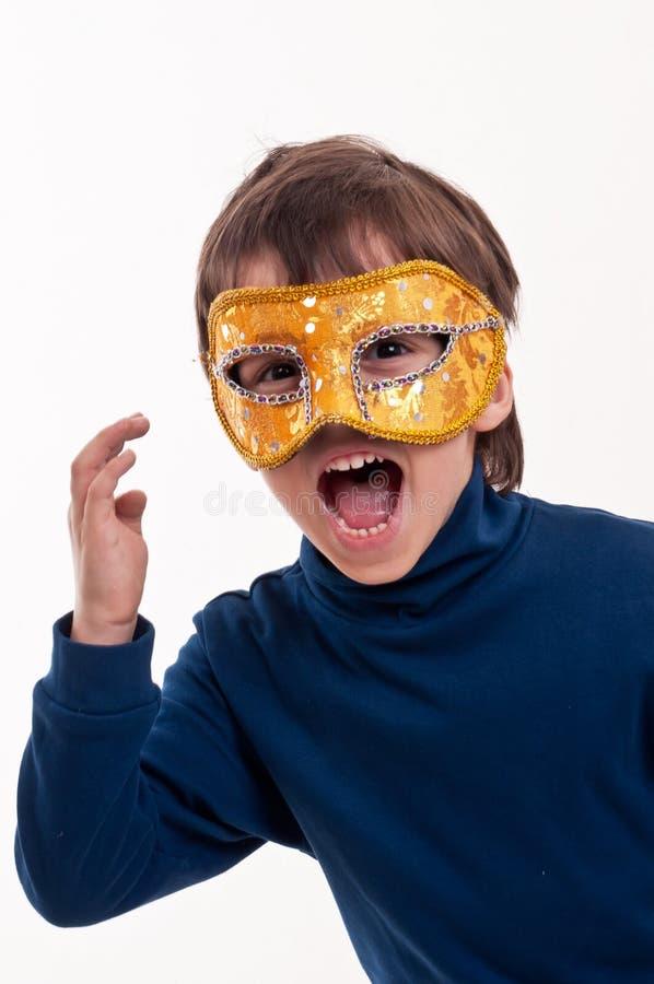 Pys som bär en guld- karnevalmaskering som låtsar för att vara en superhero royaltyfria foton