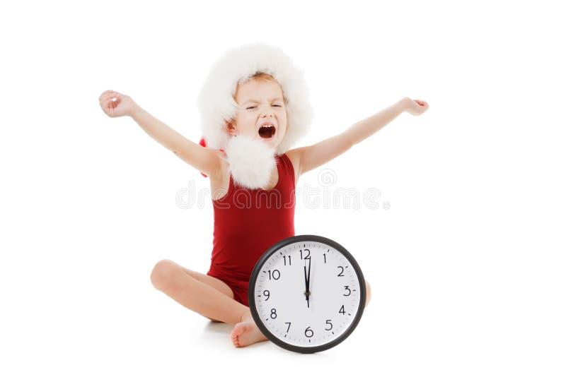 Pys som bär Santa Claus den röda hatten med klockan som isoleras på vit Julfilial och klockor fotografering för bildbyråer