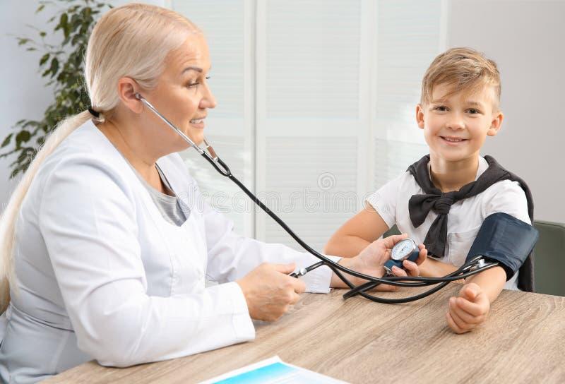 Pys som besöker doktorn i sjukhus mätande tryck för blod arkivfoto