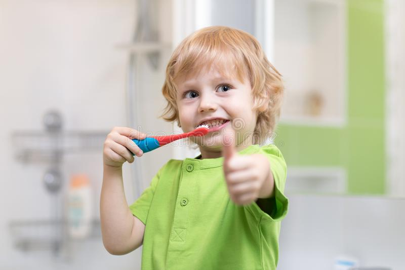 Pys som borstar hans tänder i badrummet Le upp hållande tandborste- och visningtummar för barn arkivfoton