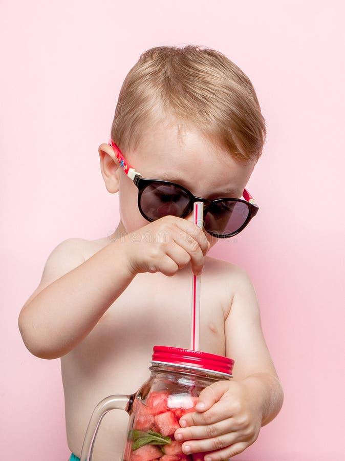 Pys som dricker ny lemonad med stycket av vattenmelon och is på rosa bakgrund royaltyfri bild