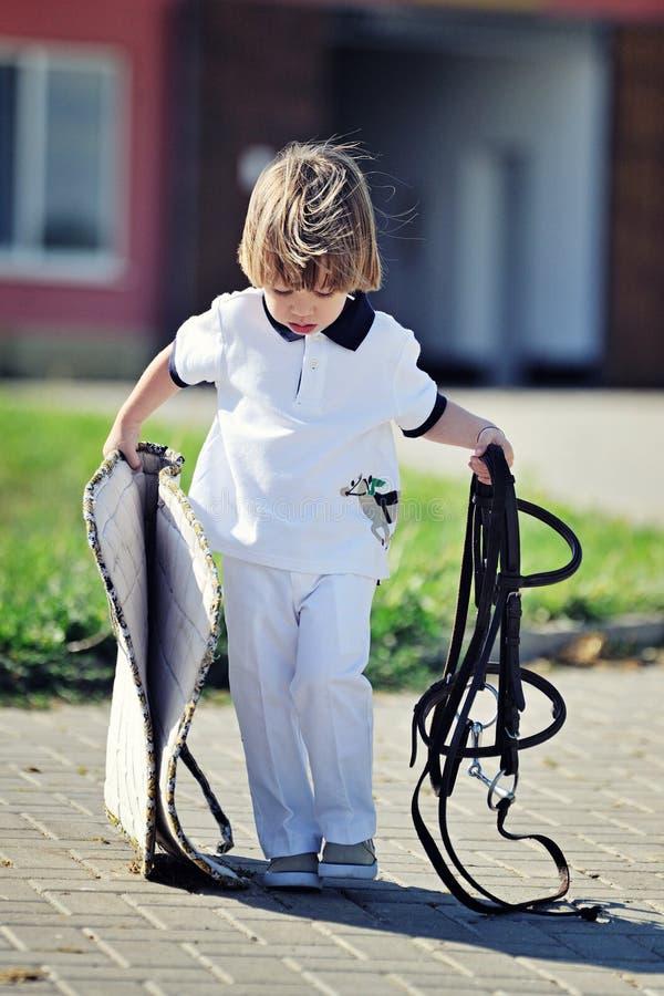 Pys som förbereder sig att sadla upp ponnyn royaltyfria foton