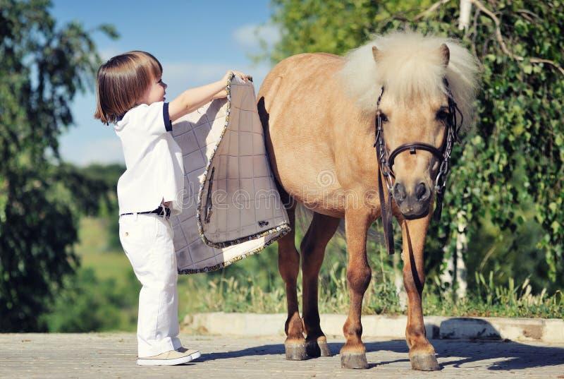 Pys som förbereder sig att sadla upp ponnyn royaltyfri foto