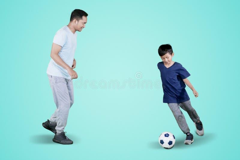 Pys som gör fotbollövningar med hans fader royaltyfri fotografi