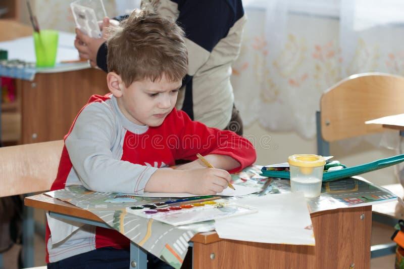 Pys som gör konstverk på skola som sitter på hans skrivbord royaltyfri bild