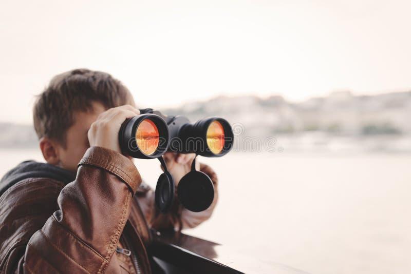 Pys som håller ögonen på och att se, stirra som söker för vid binokulärt fotografering för bildbyråer