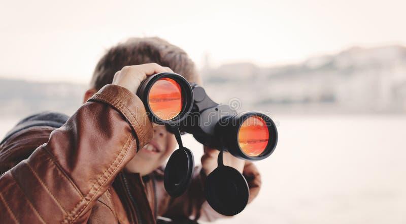 Pys som håller ögonen på och att se, stirra som söker för vid binokulärt arkivfoto