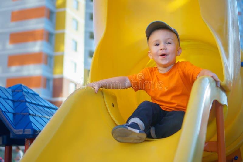 Pys som har gyckel på en lekplats utomhus i sommar Skämtsamt litet barn på en glidbana arkivfoton