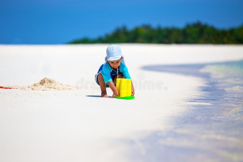 Pys som har gyckel på stranden, medan bygga en sandslott arkivbild