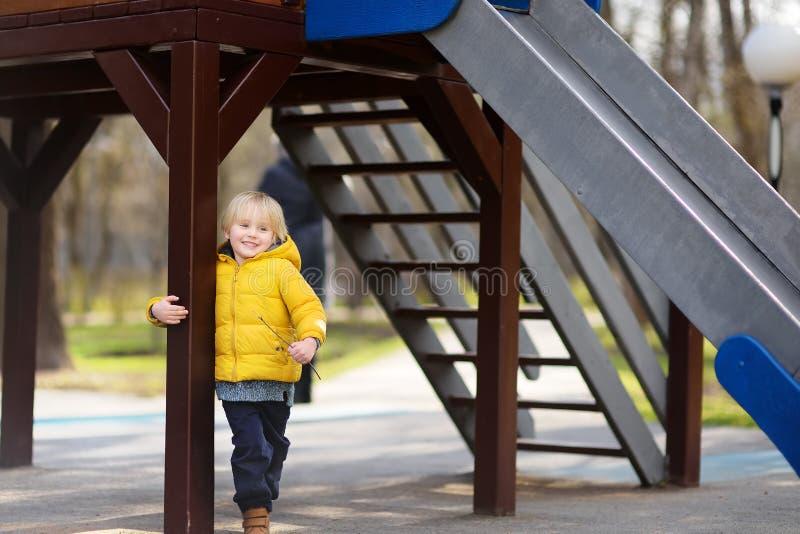 Pys som har gyckel på utomhus- lekplats på vår- eller höstdag arkivbilder