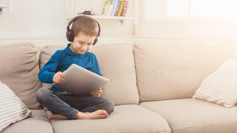 Pys som hemma använder den digitala minnestavlan på soffan royaltyfri foto